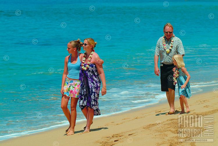 Tourist family walking on Mahaka beach, west side of Oahu