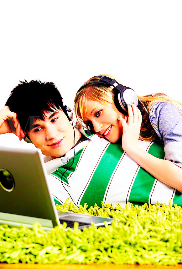 Teenage boy and girl listening to music through headphones