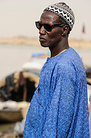 MALI, Mopti, river Niger, port with pinnace boats, market day, man with sunglasses and woolen cap / Mali, Mopti, Fluss Niger, Markttag und Warenhandel im Hafen mit Pinassen
