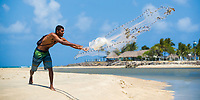 Young fisherman throwing his net in Porto de Galinhas, with beach houses and palm trees in the background, Ipojuca Pernambuco, Brazil