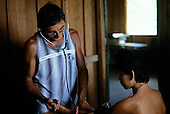 Ipixuna village, Amazon, Brazil. Funai doctor with an Arawete patient in the health post taking blood pressure.