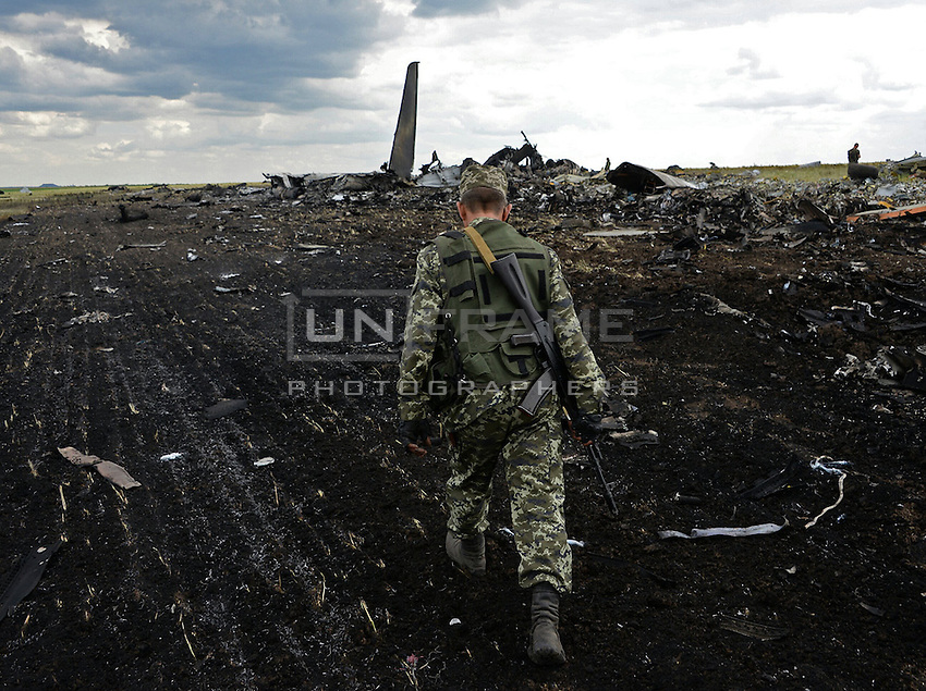 Pro-Russian militia secure the impact area of downed Ukrainian military transport plane (IL-76). Novogannivka, ( Lugansk ), Ukraine.<br /> <br /> The night before plane was shot down by anti-aircraft guns and missiles of the militia of Lugansk peoples republic causing 49 casualties between Ukriane soldiers. June 14, 2014