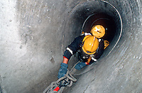 Firefighters in breathing apparatus crawling along a concrete underground tunnel where a small child has become trapped. This image may only be used to portray the subject in a positive manner..©shoutpictures.com..john@shoutpictures.com
