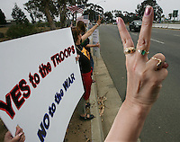 X.protest.1.0519.jl.jpg/Carol Moore of Fountain Valley gives the peace sign during a Recruting For Peace war protest held at Camp Pendleton's front gate Saturday. About 20 protesters including veterans, military families and others in the Orange County Peace Coalition met in the Oceanside Harbor's parking lot and marched over to the front gate for a peaceful protest. There reception from Marines driving into the base was mostly warm.