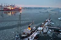 GERMANY Hamburg, container vessel in harbour at river Elbe / DEUTSCHLAND Hamburg, Containerschiff Hamburg Sued am Container terminal Burchardkai der HHLA, Blick auf Museumshafen Oevelgoenne im Winter
