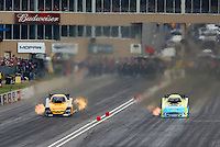Jul. 19, 2014; Morrison, CO, USA; NHRA funny car driver Bob Tasca III (right) races alongside Del Worsham during qualifying for the Mile High Nationals at Bandimere Speedway. Mandatory Credit: Mark J. Rebilas-