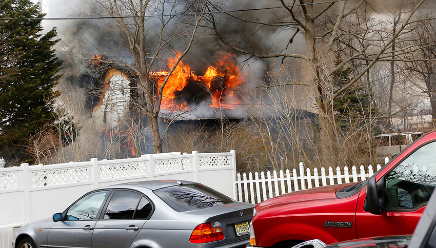 Flames blow out of the second story of a home on Pearce Avenue in Manasquan as firefighters begin battle a multiple-alarm structure fire on Easter Sunday, April 1, 2018.