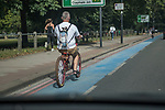 Pet dog being carried in a backpack carrier on a bicycle in south London 2021. The dog is wearing eye glasses as protection. Taken through wind screen as driving.