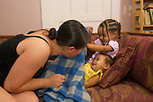 MR / Schenectady, NY. Mother (20) playing peek-a-boo with her infant daughter (girl, 10 months, African American & Caucasian). Her toddler-aged daughter (2, African American & Caucasian) joins in the game. MR: Dal6, Dal4, Dal5. ID: AL-HD. © Ellen B. Senisi
