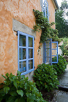 Tinted stucco and painted blue trim decorate the exterior of Casa do Castelo de Andrade, a guest house in Galicia, Spain.