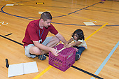 MR / Schenectady, NY. Zoller Elementary School (urban public school). Kindergarten inclusion classroom. Gym teacher helps student hold his knees down as student uses teacher-made equipment to test student flexibility. This is part of his students' yearly assessment of their physical education skills. MR: Mel16, Ram13. ID: AM-gKw. © Ellen B. Senisi.