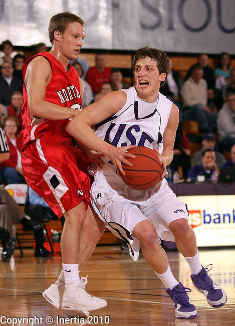 SIOUX FALLS, SD - FEBRUARY 25:  Matt Malloy #4 of the University of Sioux Falls drives against Mike Vorwald #20 of Northwestern College in the first half of their GPAC tournament game Thursday night at the Stewart Center. (Photo by Dave Eggen/Inertia)