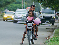 A man stops to use his cell phone while riding a motorcycle in Dili, Timor-Leste (East Timor)