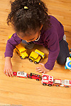Four year old girl sorting toy vehicles by type and size
