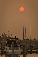 Filtered by smoke from wildfires throughout the region the sun glows above boats moored at the San Leandro Marina on San Francisco Bay on September 13, 2020.