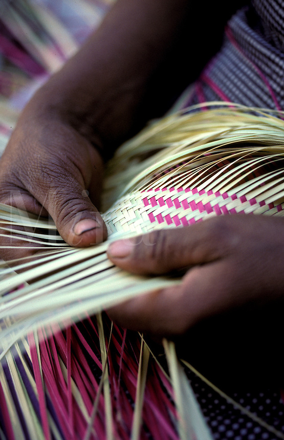 Hands making basket out reeds.