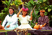 Two women dressed in traditional 19th century clothing chant with their ipus (gourd drums), while a beautiful young girl wearing white and a pink haku lei (headpiece) performs a seated hula. Photographed at Volcanoes National Park.