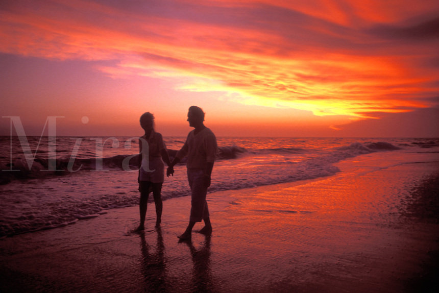 Retired Couple Walking on Beach at Sunset