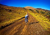 A mountain cyclist rides uphill on desolate Mana Road which winds up Mauna Kea on the Big Island of Hawaii.