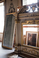 A gilded overmantel in the process of being restored rests on the bare floorboards of the drawing room