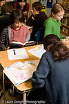 Elementary school Grade 5 classroom male and female students at work on geography social studies assignment vertical