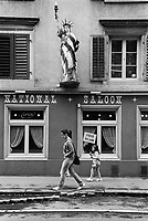 Switzerland. Canton Glarus. Glarus. Town center. A replica of the Statue of Liberty above a cafe-restaurant, called National Saloon. Free Wifi available. A mother and her daughter walk on the sidewalk. 19.08.2017  © 2017 Didier Ruef