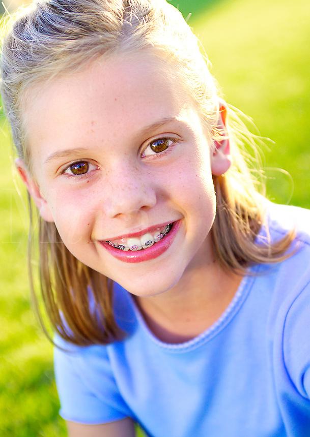 Beautiful young blonde girl smiling in summer sun