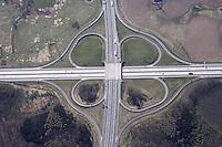 """4415/Autobahnkreuz Rostock:DEUTSCHLAND, MECKLENBURG-VORPOMMERN,  20.04.2005:Autobahnkreuz Rostock A19 - A20.  Die Bundesautobahn 20 (Abkurzung: BAB 20) – Kurzform: Autobahn 20 (Abkuerzung: A 20), auch """"Ostseeautobahn"""" oder """"Kustenautobahn"""" genannt – ist eine Autobahn in Norddeutschland. Der Spatenstich zu dieser Autobahn erfolgte 1992 an der Anschlussstelle Wismar-Mitte. Die Baukosten betrugen 1,9 Milliarden €. Am 7. Dezember 2005 eroeffnete Bundeskanzlerin Angela Merkel..Die Erfindung der planfreien Kreuzung geht auf den amerikanischen Bauingenieur Arthur Hale zurueck, dessen Kleebatt-Kreuz am 29. Februar 1916 beim Patentamt eingetragen wurde. In Europa gilt der Schweizer Willy Sarbach als Erfinder, der 1927 Plaene von einem 'Kleeblatt' in Basel vorstellte, die am 15. Oktober 1928 als Patent eingetragen wurden. Davon unabhaengig stellte Edward Delano aus Philadelphia, inspiriert durch die Verkehrsführung in Buenos Aires, bei der statt direktem Linksabbiegen durch dreimaliges Rechtsabiegen ein Block umfahren wurde um nach links abzubiegen, das gleiche Konzept vor. Dieses führte 1928 zum Bau des ersten echten Autobahnkreuzes der Welt bei Woodbridge, New Jersey, das bis heute existiert..In den 30er Jahren, als man in Deutschland im großen Stil den Bau von Autobahnen plante, wurde das Thema Autobahnknotenpunkte akut. 1936 wurde das Schkeuditzer Kreuz bei Leipzig als erstes Autobahnkreuz Europas in Betrieb genommen und 1938 fertiggestellt..Das Kamener Kreuz wurde 1937 eingeweiht, hatte aber noch keine Funktion, da die A 1 noch nicht fertiggestellt war. Erst 1965 wurde das als Kleeblatt gebaute Autobahnkreuz in vollem Umfang in Betrieb genommen..Bereits 1933 wurde das Frankfurter Kreuz konzipiert und in den Jahren 1939–1941 vorlaeufig trassiert, konnte aber erst nach dem Zweiten Weltkrieg fertig gestellt werden und wurde am 10. Juli 1956 durch den damaligen Verkehrsminister Hans-Christoph Seebohm dem Verkehr uebergeben. Luftbild, Luftansicht."""