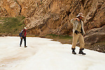 Snow Leopard (Panthera uncia) biologists, Shannon Kachel and Khalil Karimov, walking over ice in canyon, Pikertyk, Tien Shan Mountains, eastern Kyrgyzstan