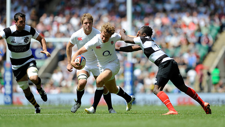 Billy Twelvetrees of England is tackled by Marco Wentzel of the Barbarians during the match between England and Barbarians at Twickenham on Sunday 26th May 2013 (Photo by Rob Munro)