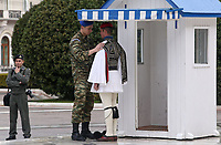 Pictured: A soldier helps adjust the uniform of a Tsolias or Evzonos of the Presidential Guard on the steps of the Monument to the Unknown Soldier outside the Greek Parliament in Syntagma Square, Athens, Greece.<br /> Re: Official visit of German Chancellor Angela Merkel  to Athens, Greece.