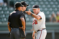Rocket Wheeler (18), manager of the Rome Braves, has a word with home plate umpire Harley Acosta, left, and umpire Chris Silvestri after a close call on a rundown in Game 1 of a doubleheader against the Greenville Drive on Friday, August 3, 2018, at Fluor Field at the West End in Greenville, South Carolina. Rome won, 7-6. (Tom Priddy/Four Seam Images)