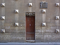 A relatively modest doorway marks the side entrance to the building, its walls punctuated with a decorative stone design