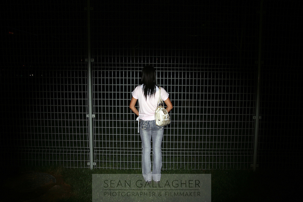 CHINA. Beijing. A woman looks through a fence near the Olympic stadium. 2008