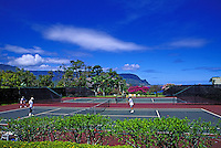 People enjoy a set of tennis amid flowering trees, mountains and brilliant blue sky at the Hanalei Bay Resort on Kauai's north shore.