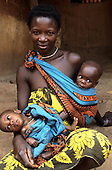 Kisamba, Tanzania. Proud mother with her twin babies, one in a sling, the other on her knee.