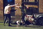 © Joel Goodman - 07973 332324 . 01/01/2017 . Manchester , UK . A shirtless man and a woman clash as another man lies in the gutter . A fight involving several men and women spills over on to St Mary's Parsonage . People on a night out in Manchester City Centre , after midnight on January 1st 2017 . Photo credit : Joel Goodman