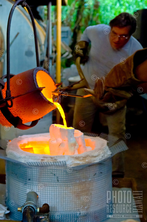 Sculptor Steve Smeltzer (foreground, with gloves) and artist Charlie Corda (background) pour molten bronze into molds at the Tom Faught Studio, Haiku, Maui.