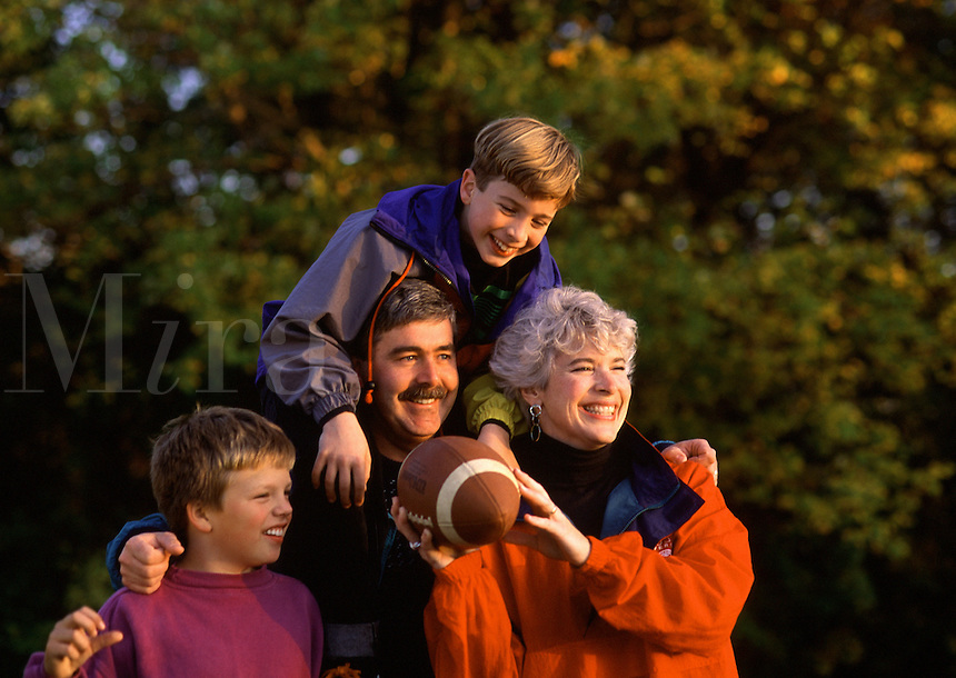 A smiling family of parents and sons out playing football together.