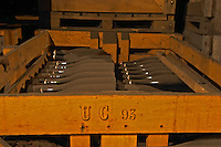 In the wine cellar: Dusty dust covered bottles lying in a wooden crate after the secondary fermentation in bottle. The bottles are sealed with a crown cap. The crate is marked UC 93 (presumably Union Champagne, vintage 1993), the Union Champagne cooperative, also called Champagne de Saint Gall in Avize, Cote des Blancs, Champagne, Marne, Ardennes, France