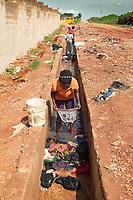 Nigeria. Enugu State. Enugu. Women clean their laundry in a sewer on the road. Enugu is the capital of Enugu State, located in southeastern Nigeria. 2.07.19 © 2019 Didier Ruef