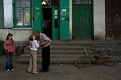 Dobromil, Urkaine.May 31, 2005 ..In front of village store a man kisses his daughter who has just returned from the last day of school in a farming village near the Polish border.....