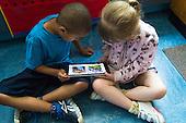 MR / Schenectady, NY. Zoller Elementary School (urban public school). Kindergarten classroom. Students read an eBook / app on an iPad. Left: boy, 5, African American; Right: girl, 6. MR: Ste14, Man6. ID: AM-gKw © Ellen B. Senisi.