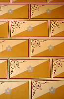 A detail of the 19th century hand-painted brick and floral motif by Eugène Viollet-le-Duc on a wall at Château de Roquetaillade