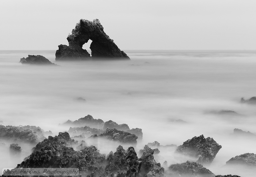 A ghostly mist seems to shroud the rocks and water at Little Corona in Corona Del Mar (Newport Beach), California.  This long-exposure shot was taken at dusk, so the wave action blended together into a soft, almost-fog like look.  It almost looks like you could walk out to the distinctive Arch Rock offshore (but you can't).  I'm also pleased to report that a bird stood still long enough on the left side of the arch rock to appear in the exposure.