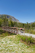 Person riding a bike along the Franconia Notch Bike Path with Cannon Mountain in the background during the spring months in Lincoln, New Hampshire. The Franconia Bike Path is a multi use path.