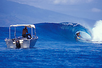 Local surfing the tube on a perfect right in clear blue water with friend video taping, Moorea, Society Islands, French Polynesia