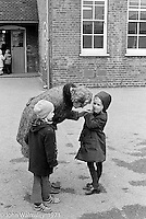 PLayground helper listening to a child, Darell Road Primary School, London.  1973
