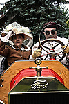 Two people driving a vintage race car