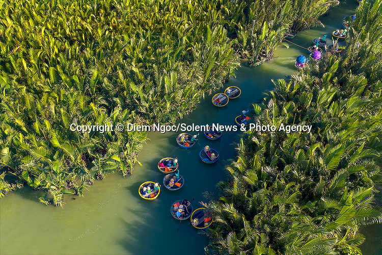 "Pictured: Circular boats make their way through a coconut forest.   Tourists bundle into the bamboo baskets before exploring the 100-hectare forest with a guide, gliding through the channels of water and becoming surrounded by the coconut trees.<br /> <br /> Amateur photographer Diem Ngoc pictured the boats in the Bay Mau coconut forest in Hoi An, Vietnam.   The 42 year old Customs Officer, from Ho Chi Minh City, Vietnam, said: ""Travelling through the coconut forest is an amazing experience for the visitors.   SEE OUR COPY FOR DETAILS<br /> <br /> Please byline: Diem Ngoc/Solent News<br /> <br /> © Diem Ngoc/Solent News & Photo Agency<br /> UK +44 (0) 2380 458800"
